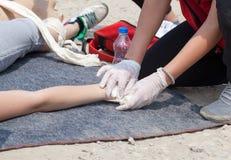 Person med paramedicinsk utbildning som hjälper en sårad person efter olycka Royaltyfria Bilder