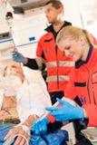 Person med paramedicinsk utbildning som injicerar den sjuka tålmodign i ambulanshjälpmedel Royaltyfria Foton