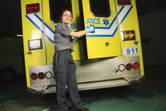 Person med paramedicinsk utbildning som stänger dörren av ambulansen Arkivbild