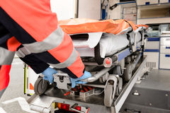 Person med paramedicinsk utbildning som ut drar gurneyen från ambulansbilen Royaltyfri Fotografi