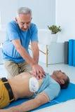 Person med paramedicinsk utbildning som utför återuppväckande på patient Fotografering för Bildbyråer