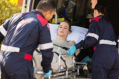 Person med paramedicinsk utbildningpatientambulans Arkivfoton