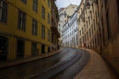 Person med paraplyet som går upp den gamla stadsgatan arkivbilder