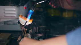 Jeweler, goldsmith in a professional jewelry workshop melts metal with burner at a jewellery workshop. A person melts metal with burner at a jewellery workshop stock footage