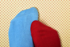 Person with mismatched socks. Closeup of the feet of someone with a blue sock in one foot and a red sock in the other, on a dot patterned background Royalty Free Stock Photography