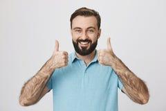 Person mit den netten Bart- und Schnurrbartdaumen zeigen bis seine positive Antwort, die nahe weißer Wand steht Reifes Mannestrag Stockfotografie