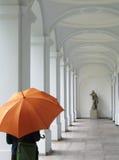 Person mit einer orange Regenschirmstellung Stockfotografie