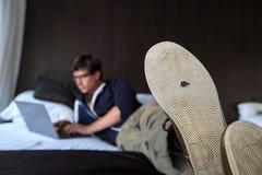 Person mit Loch im einzigen Schreiben des Schuhes auf einem Laptop Stockbilder