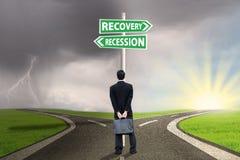 Person mit Wegweiser der Rezessions- und Wiederaufnahmefinanzierung Stockfoto