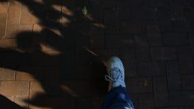 Person mit weißen Schuhen und Jeans gehend auf eine Ziegelsteinstraße stock video footage