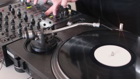 A person mixing music on an audio mixer with a vinyl rotating beside it stock video