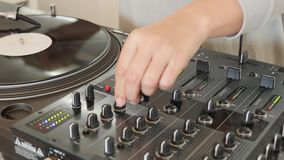 A person mixing music on an audio mixer with a vinyl rotating beside.  stock video footage