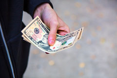 Person with the Money. Person hold the Money on the Street closeup Royalty Free Stock Images