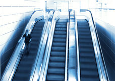 Person in motion on escalator Stock Photo