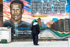 Person observing the mural dedicated to Benjamin O'Garro. Stock Images