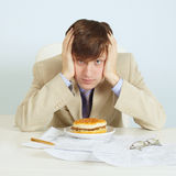 Person at office on workplace with a hamburger Royalty Free Stock Image