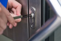 Person Opening Door With Lockpicker arkivfoto
