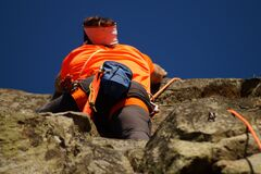 Person in Orange Shirt Climbing Rock during Daytime Stock Image