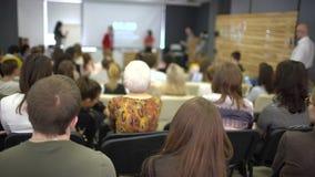 Person på forumet som löser ekonomiska frågor av samtiden och som ser problem Kvinnan lär i klassrum Högtalare i grupp stock video