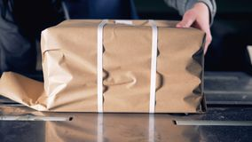 A person is packing a sheaf of magazines into craft wrapping paper. 4K stock video