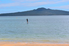 Person paddle boarding in mission bay in Auckland New Zealand. AUCKLAND - JAN 11 2016:Person paddle boarding in mission bay in Auckland New Zealand.It's an Royalty Free Stock Photo