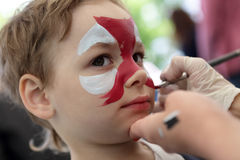 Person painting boy face. At the amusement park Stock Photography