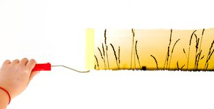One person painting grass on a white wall with a roller brush. Person painting grass on a white wall with a roller brush Royalty Free Stock Image