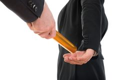 Person passing a golden relay baton to another person. Close-up Of A Person Passing Golden Relay Baton To Another Person stock images