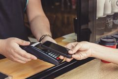 Person paying pay through smartphone using NFC. Technology in outdoor cafe Stock Photo