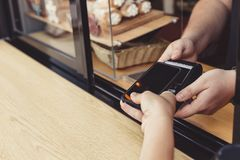 Person paying pay through smartphone using NFC. Technology in outdoor cafe Royalty Free Stock Photos