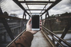 Person with phone on bridge