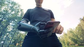 Person with a phone outdoors. Human with a robot arm. Handicapped person with a bionic hand works with a phone , standing in the park