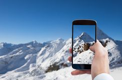 Person photographing snowy mountain landscape Royalty Free Stock Image