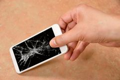 Person picking broken smart phone with cracked screen on the flo. Or at home stock image