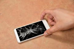 Person picking broken smart phone with cracked screen on the flo. Or at home royalty free stock photography