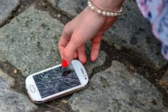 Person Picking Broken Smart Phone Cracked Screen of the Ground.  stock photos