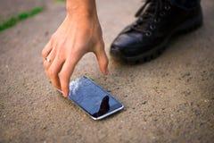Person Picking Broken Smart Phone Cracked Screen on Ground. Person Picking Broken Smart Phone with Cracked Screen on Ground royalty free stock photos