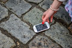 Person Picking Broken Smart Phone Cracked Screen of the Ground.  stock images