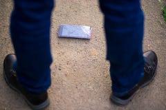 Person Picking Broken Smart Phone Cracked Screen on Ground. Person Picking Broken Smart Phone with Cracked Screen on Ground royalty free stock photography
