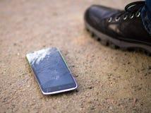 Person Picking Broken Smart Phone Cracked Screen on Ground. Person Picking Broken Smart Phone with Cracked Screen on Ground stock photo