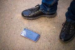 Person Picking Broken Smart Phone Cracked Screen on Ground. Person Picking Broken Smart Phone with Cracked Screen on Ground royalty free stock images