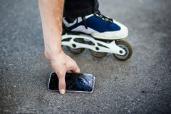 Person picking broken smart phone with cracked screen. Of the ground stock images