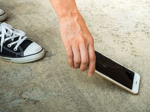 Person Picking Broken Smart Phone of Ground. Person Picking Broken Smart Phone (Cracked Screen) of the Ground royalty free stock photography
