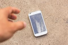 Person Picking Broken Smart Phone. Cracked Screen of the cement floor Stock Images
