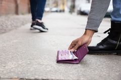 Person Picking Up Lost Purse. Close-up Of A Person`s Hand Picking Up Lost Purse royalty free stock image