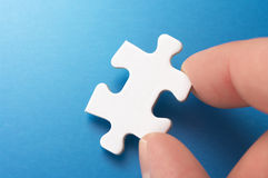 A person picking up one puzzle pieces. Stock Photo