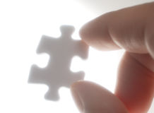 A person picking up one puzzle pieces against the light.(horizon Stock Images