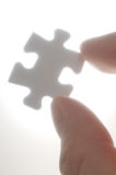 A person picking up one puzzle pieces against the light.(vertica Royalty Free Stock Photo