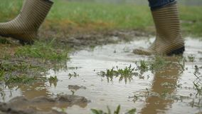 Person with pink boots and blue umbrella splashing in the puddle. girl in raincoat and rubber boots jumping into puddle. Rubber boots comes in a puddle HD stock photo