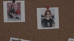 Person pins two photos of young woman on cork board inside stock footage